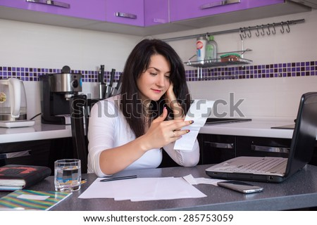 stressed young woman is doing banking and administrative work holding bills at home - stock photo