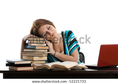 Stressed young woman sitting at a table among books and  laptop on a white background - stock photo