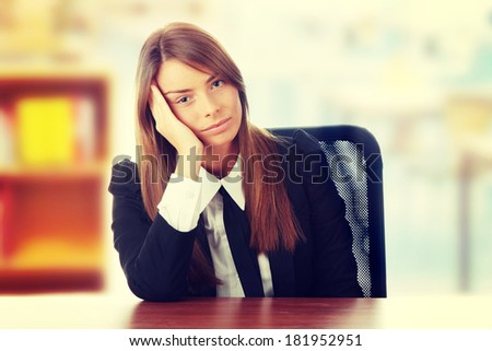 Stressed young woman sitting behind a desk - stock photo