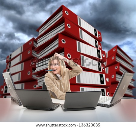 Stressed young woman using multiple computers, with piles of folders on the backgrounds - stock photo