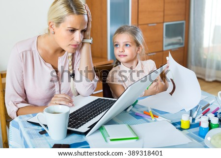 Stressed young woman working from home, little daughter asking for attention - stock photo