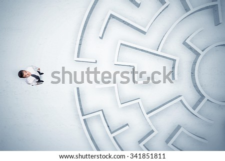 Stressful business man looking at circular maze with nowhere to go - stock photo