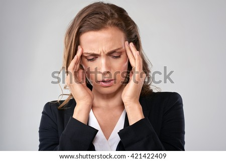 Stressful business woman massages her temple to ease her tension headache migraine head pain - stock photo