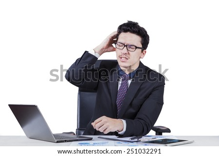 Stressful caucasian businessperson scratching his head while working on desk, isolated on white - stock photo