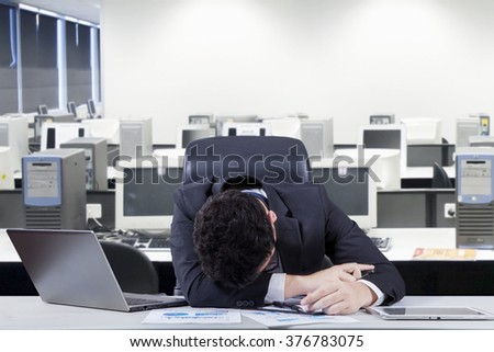 Stressful male entrepreneur wearing formal suit and sleeping on the table with laptop and documents, shot in the office room