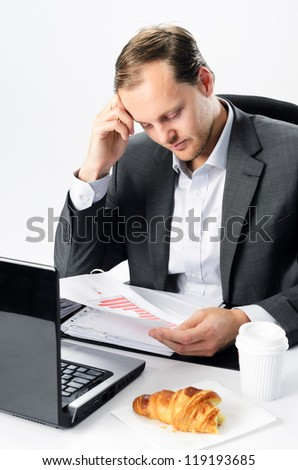 Stressful man under pressure at work, half eaten breakfast pastry croissant and coffee - stock photo