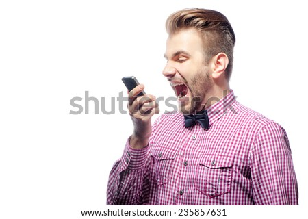 Stressful phone talk. Furious young man in shirt and  bow tie shouting at cellphone while standing isolated on white - stock photo