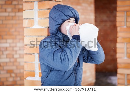 Stressful Teenager breathe into paper bag near building in winter