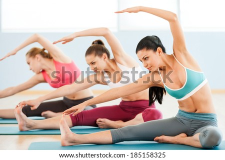 Stretch to the right! Three beautiful young women in sports clothing exercising together while sitting on exercise mats