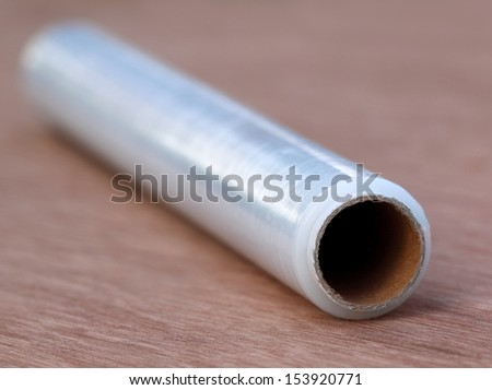 Stretch wrapping film on wooden surface - stock photo