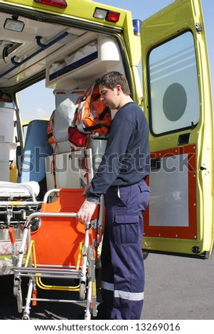 Stretcher bearer carrying an invalid chair with background an ambulance litter. - stock photo