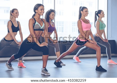 Stretching after great workout. Beautiful young women with perfect bodies in sportswear exercising with smile while standing in front of window at gym - stock photo