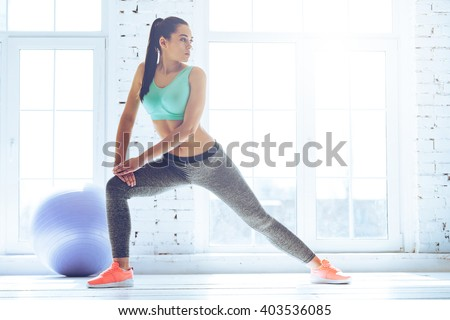 Stretching after great workout. Young beautiful young woman in sportswear doing stretching while standing in front of window at gym - stock photo