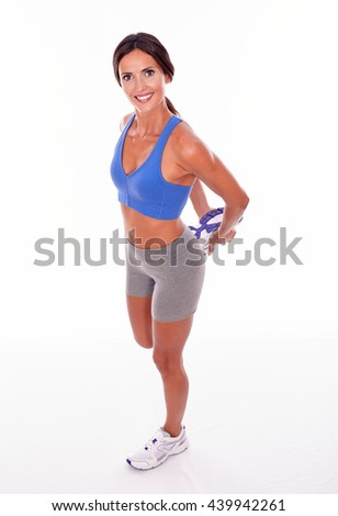 Stretching brunette woman holding a leg behind her with both hands while looking up at camera smiling wearing blue and grey casual clothing, isolated - stock photo
