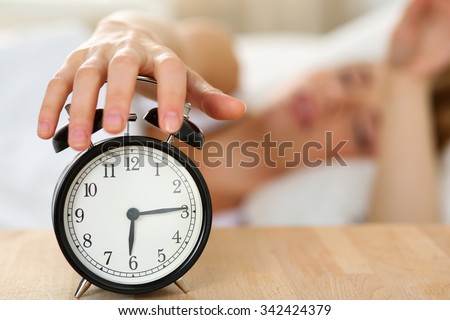 Stretching hand of sleepy young woman trying kill alarm clock ringing awakening early morning. Early wake up, not getting enough sleep, getting work concept. Female arm willing turn alarm sound off - stock photo