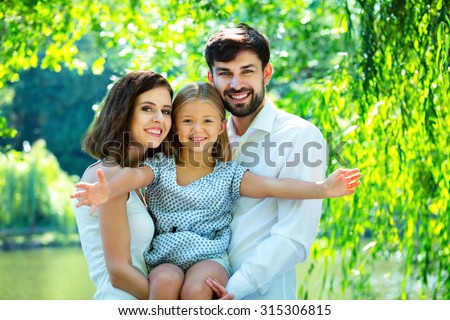 Stretching hands of happy daughter with parents. Rest time of family. Outdoor picnic under green trees.