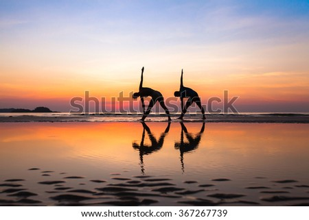 stretching on the beach at sunset, yoga exercises, silhouettes of couple