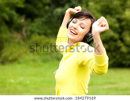 stretching pretty young lady listening to music in the park - stock photo
