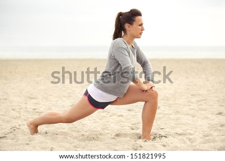 Stretching woman in outdoor exercise smiling happy doing yoga stretches after running. Beautiful happy smiling sport fitness model outside on summer day. - stock photo