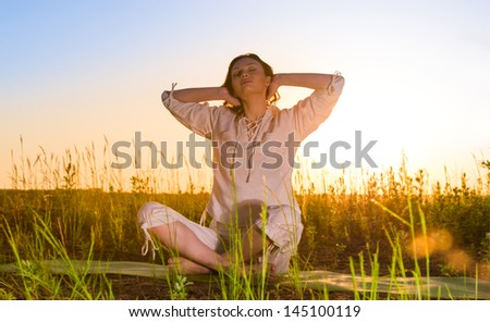 Stretching woman in outdoor exercise smiling happy doing yoga stretches. Beautiful happy smiling sport fitness model outside on summer / spring day