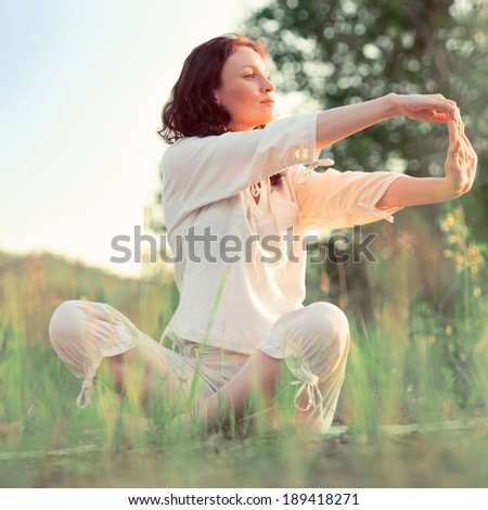 Stretching woman in outdoor exercise smiling happy doing yoga stretches. Retro filter photo