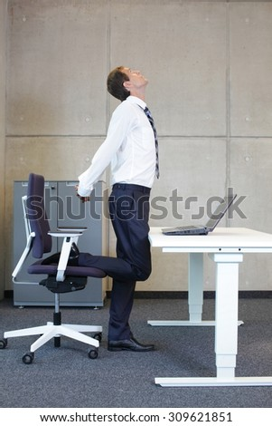 stretching - young businessman in standing position taking short break for exercise in office work