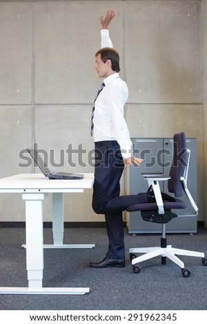stretching - young businessman taking short break for exercise in office work