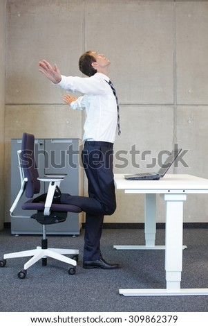 stretching - young businessman taking short break for exercise in office work - stock photo