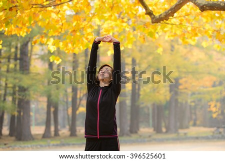 Stretching young woman under the autumn trees. - stock photo