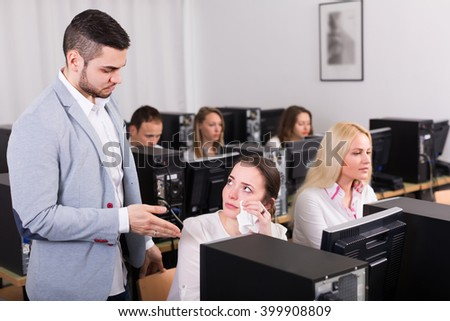 Strict boss and crying female clerk at open space working area. Selective focus  - stock photo