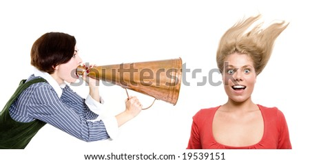 strict boss shouting at businesswoman through old style loudspeaker. hi key - stock photo