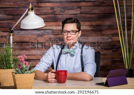 Strict boyish woman in suspenders at desk with a red coffee cup - stock photo
