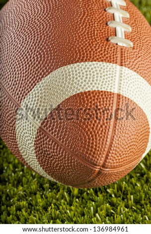 Strict close up of a football over green grass