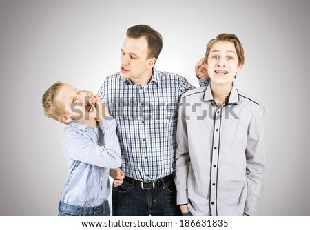 Strict father punishes his sons. - stock photo