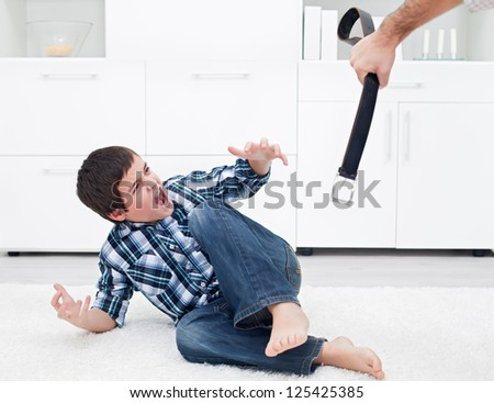 Strict father punishing his son with a belt - stock photo