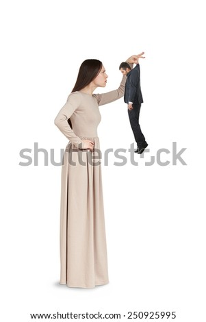 strict young woman to examining small man. isolated on white background - stock photo