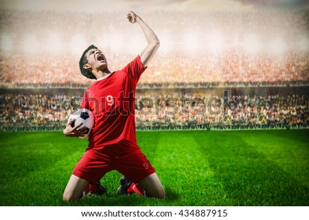 striker soccer football player in red team concept celebrating goal in the stadium during match   - stock photo