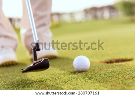 Striking it gently Close up of man going to putt ball into hole with help of golf club - stock photo