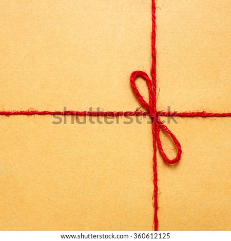 string and brown paper parcel red string bow against brown wrapping paper
