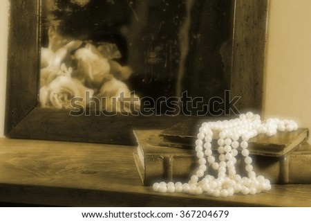 String of pearls, books and antique mirror with roses.  Focus on pearls. Vintage effect. - stock photo