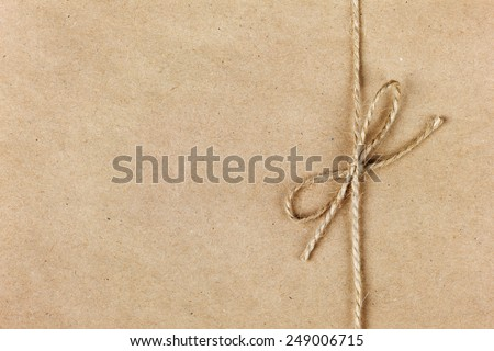 string or twine tied in a bow on kraft paper background