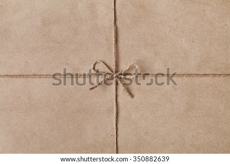 String or twine tied in a bow on kraft paper texture