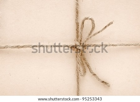 String tied in a bow on a brown paper - stock photo