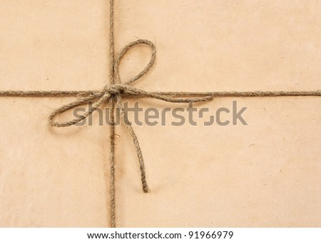 String tied in a bow on a brown recycled paper - stock photo