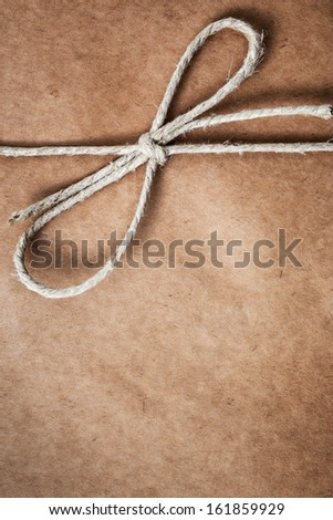 String tied in a bow, over brown package paper - stock photo