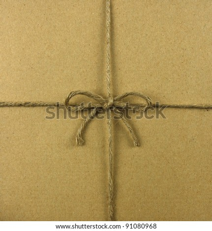 String tied in a bow, over brown recycled paper - stock photo