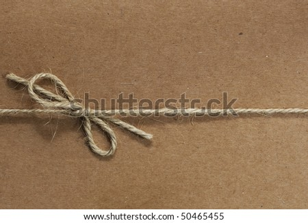 String tied in a bow, over brown recycled paper.  Great textures in the twine and paper. - stock photo