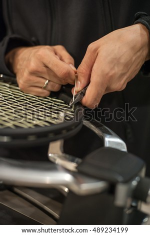 Stringing tennis racket. Tennis stringer tying knots and cutting string with pliers