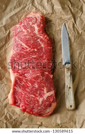 Strip loin steak on butcher paper with an old knife. - stock photo