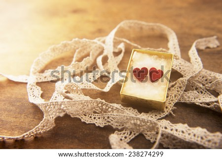 Strip of white lace and golden box with two hearts on a wooden work table. warm lighting.  - stock photo
